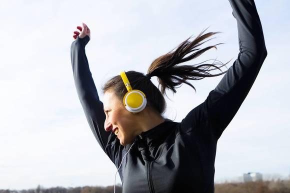 Woman in headphones dancing outdoors