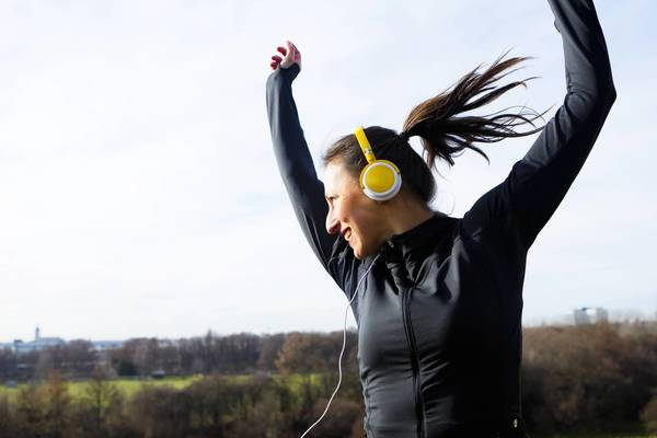Woman in headphones dancing outdoors