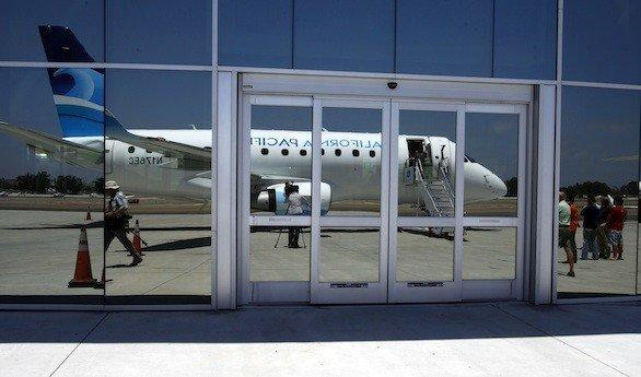 A California Pacific Airlines jet, reflected in the windows of McLellan-Palomar Airport near Carlsbad, Calif.