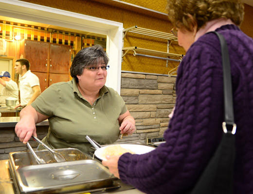Lisa Makatura of Pen Argyl, left, serves dinner to guests. The third New Years Day Pork & Sauerkraut Dinner was held at the Blue Valley Farm Show Fairgrounds in Bangor Tuesday.