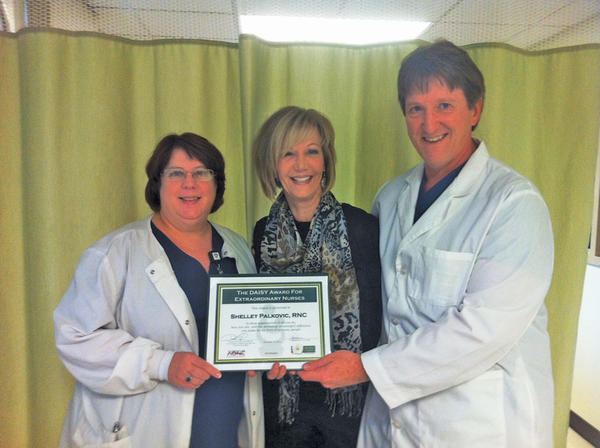 Shelley Palkovic, center, City Hospital's third-quarter recipient of the DAISY Award For Extraordinary Nurses, receives her award from Melanie Riley, left, nursing director of obstetrics, and Steve Folmer, representing the Work Life Council.