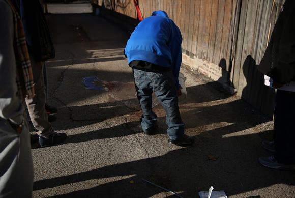 Friends clean up alley where man was shot to death on West Side. Tribune photo