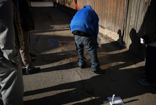 Friends of Octavius Dontrell Lamb, 20, clean his blood from the alley where he was fatally shot in the throat in the 700 block of North Noble Street in the West Town neighborhood early today. E. Jason Wambsgans, Chicago Tribune