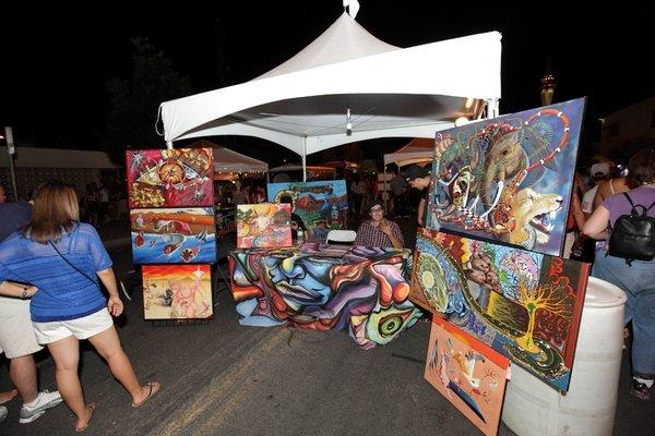 An artist displays his paintings at a booth on a downtown Las Vegas street during the city's First Friday celebration of the arts.