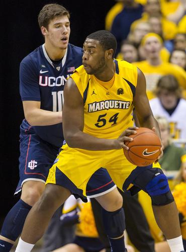Marquette forward Davante Gardner holds the ball away from UConn forward Tyler Olander during the first half.