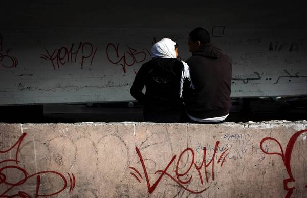 An Egyptian couple sit under a bridge in Cairo. Some young Egyptians say they are considering leaving the country because they are dismayed by postrevolutionary events.