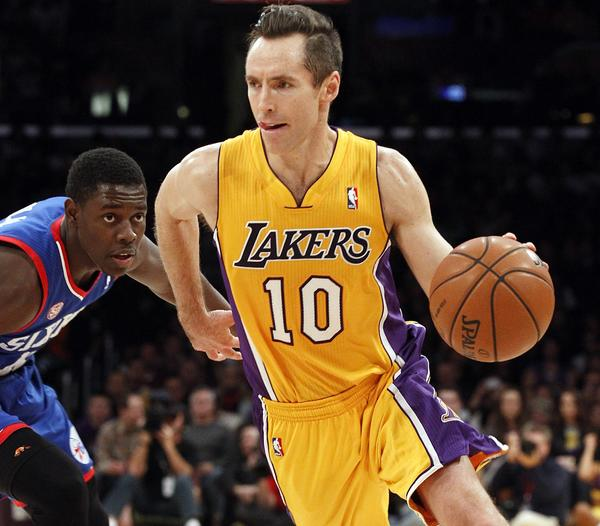 The Lakers' Steve Nash dribbles around 76ers guard Jrue Holiday in the second quarter of their game at Staples Center.