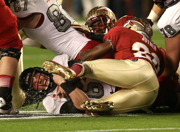 Northern Illinois quarterback Jordan Lynch is tackled hard by Florida State's Lamarcus Joyner.