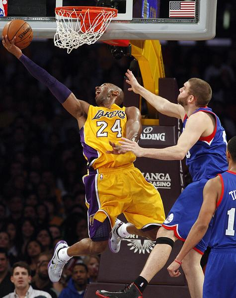 Kobe Bryant goes around Spencer Hawes for two in the fourth quarter of the Lakers-Philadelphia 76ers game at Staples Center.