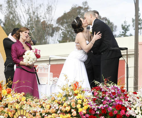 A married couple kisses atop the Farmer's Insurance Float at the 2013 Rose Parade in Pasadena on January 1, 2013.