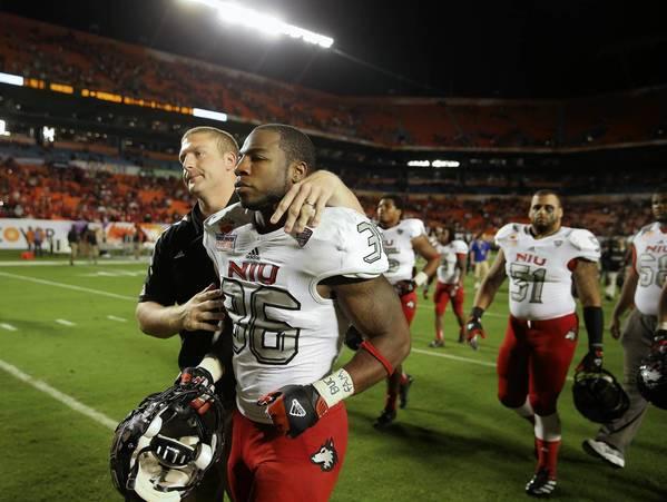 Dejected Northern Illinois Huskies linebacker Tyrone Clark (36) walks off the field after losing to Florida State in the Orange Bowl at Sun Life Stadium.