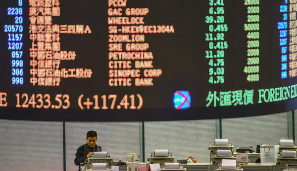 "A trader walks the floor of the Hong Kong Stock Exchange as share prices are flashed above on January 2, 2013. Hong Kong shares ended 2.89 percent higher after the US Congress approved a deal to avert the ""fiscal cliff"" of tax rises and spending cuts, with the benchmark Hang Seng Index rising 655.06 points to close at 23,311.98."