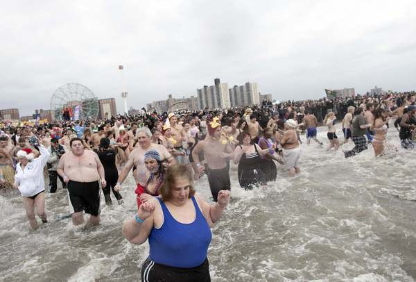 People taking part in the Coney Island Polar Bear Club's annual New Year's Day Polar Bear Swim enter the water in New York's Coney Island January 1, 2013.  The Coney Island Polar Bear Club is the oldest winter bathing organization in the U.S. and every New Years Day holds the winter plunge which attracts thousands of participants.
