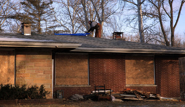 TIm Pasqual works on covering a huge hole in the roof of a house ravaged by fire on the 4700 block of Iroquois Road in Algonquin. An elderly man died in the fire.