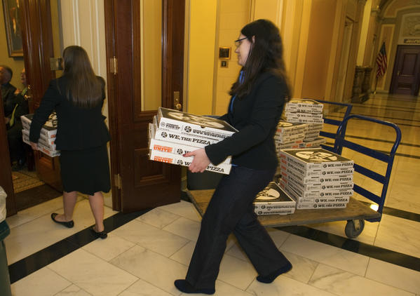 "Unidentified aides deliver pizza to House Democrats in a conference room at the Capitol Building. The Senate's version of the ""fiscal cliff"" bill was adopted by the House in a late night session despite the majority of House Republicans voting against the Bill."