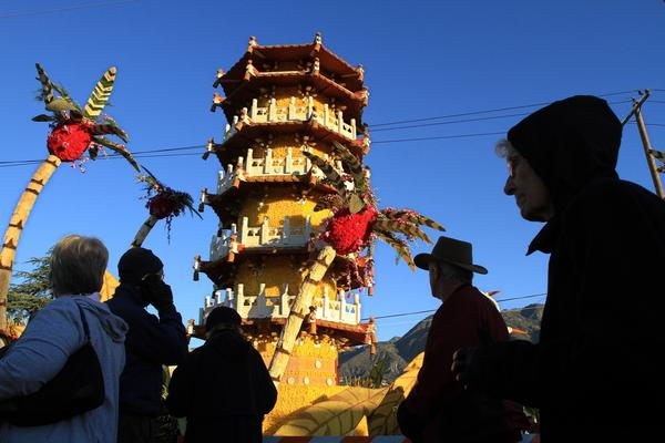 At the end of the Rose Parade route in Pasadena, visitors look at the China Airlines entry, Cycling Through Paradise.