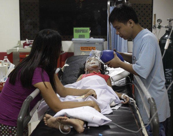 Seven-year-old Stephanie Nicole Ella lies in a bed Tuesday as her parents aid in giving her life support while being treated at the East Avenue Medical Center in suburban Quezon city, north of Manila.