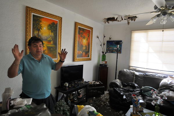 Xavier Rubio surveys the damage caused by a fire that sparked on New Year's Day inside the apartment unit next to his.