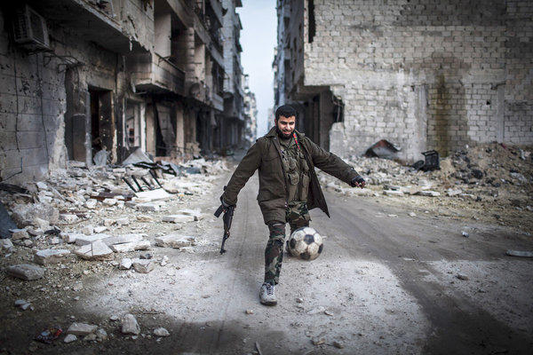 A Syrian rebel kicks a soccer ball in the Saif al-Dawlah neighborhood of Aleppo. The United Nations estimated Wednesday that more than 60,000 people have been killed in Syria's 21-month-old uprising.