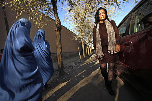 Women in burkas stare at Fereshta Kazemi with her bare legs and uncovered head in Old Kabul's Shar-e-Kohna neighborhood.