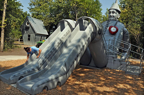 Haley Rheault, an Aberdeen Parks, Recreation and Forestry employee, on Monday morning cleans scuff marks off the new Tin Man slide at the Land of Oz in Storybook Land. Kids had a chance to use the slide over the weekend, and it was dedicated Monday afternoon. American News Photo by Anita Meyer taken 8/27/2012