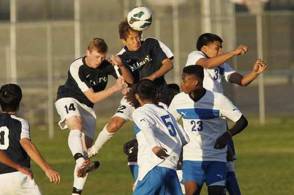 Marina's Trevor Anderson (14) and Christian Cordell (12) go up for a header during a game at the Marina Holiday Classic against Garey on Friday.