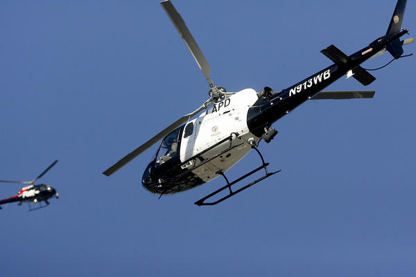With a news helicopter in the background, a Los Angeles Police Dept. Air Support helicopter helped Glendale PD SWAT officers search for a home-invasion robbery suspect west of Concord St. and Patterson Ave. in Glendale on Wednesday, January 3, 2013.