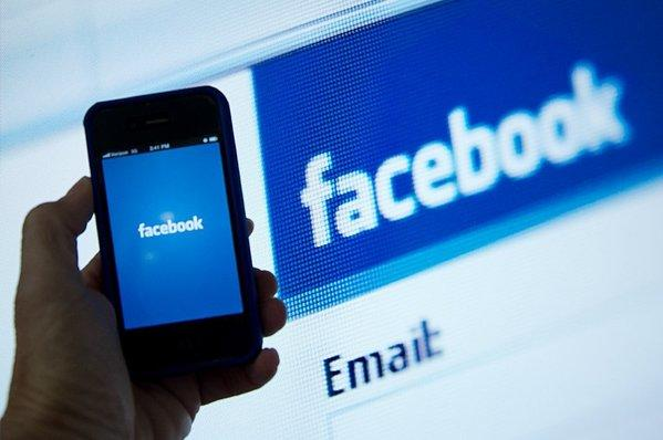An iPhone displaying the Facebook app's splash screen in front of the login page.