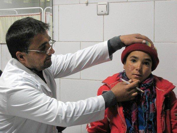 Dr. Najibullah Najib examines 13-year-old Rohullah Saleh Zada in Kabul, Afghanistan. Rohullah has scarring on his face from a disease called leishmaniasis, a common complaint among Najib's plastic surgery patients.