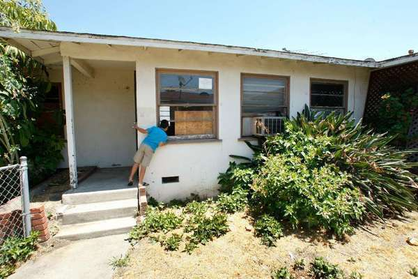 A neighbor peaks into an unoccupied, foreclosed home in East Los Angeles.