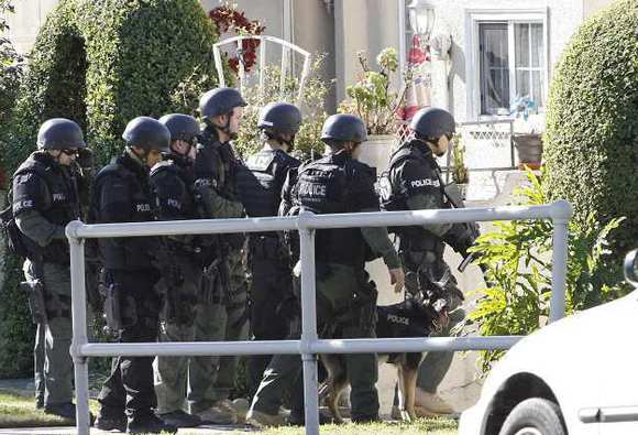 Glendale SWAT officers prepare to enter a backyard in the 600 block of West Concord St. to search for a home invasion robbery suspect on Wednesday, January 2, 2013.