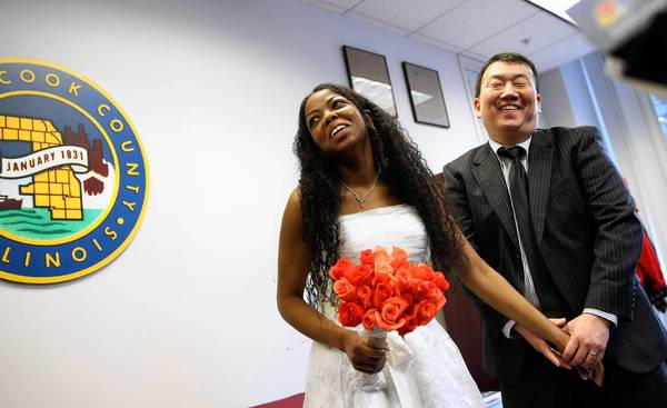 Stephen Pyo and his bride, Angela Marie McKinney, smile Wednesday after being married by Cook County Clerk David Orr in his office in Chicago. They were the first couple married in Cook County this year.