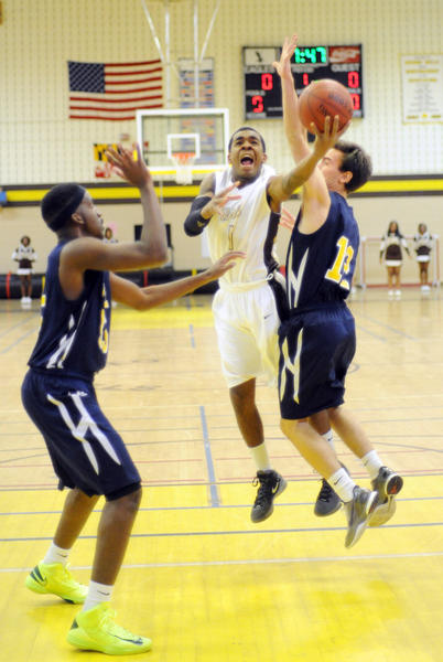 Owings Mills senior Jawon Johnson knifes between Catonsville's Jamal Tyson, left, and Kevin Sheppard on his way to a three-point play for the first points of the Eagles' 76-43 triumph Wednesday night.