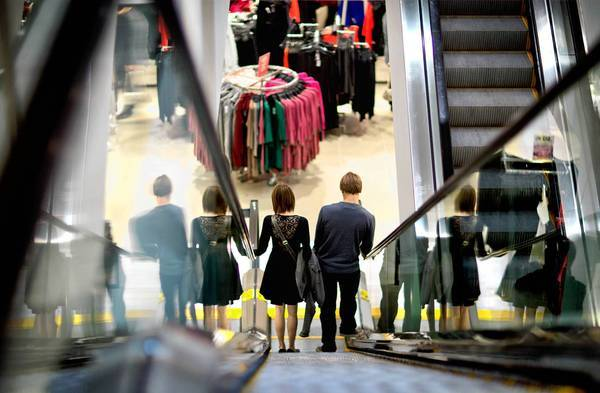 A couple descend an escalator while shopping at an H&M store in Atlanta. As of Tuesday working Americans saw a tax on their paychecks rise to 6.2% from 4.2% last year. Economists estimate that this could strip $115 billion in disposable income from the economy this year.