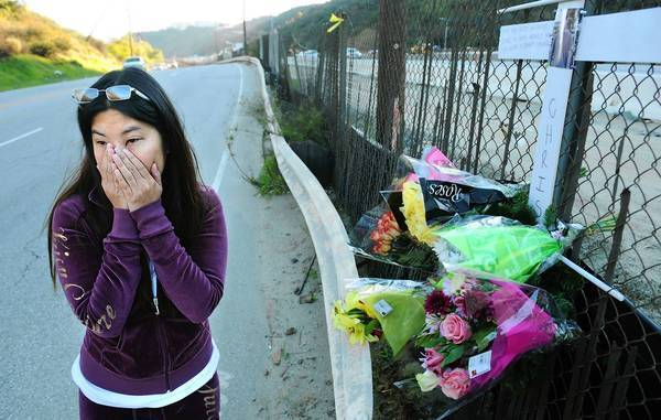 Frances Merto, the girlfriend of photographer Chris Guerra, stands at a memorial along Sepulveda Boulevard near Getty Center Drive. Guerra was struck by a vehicle and killed Tuesday night after taking pictures of Justin Bieber's car.