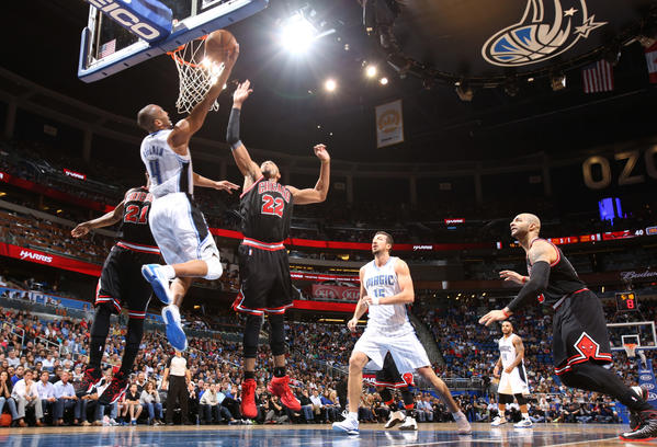 Orlando guard Arron Afflalo (4) puts in a reverse layup between Chicago's Jimmy Butler (21) and Taj Gibson (22) during the first half of the Magic's game against the Bulls in Orlando, Fla.