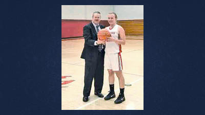 Rockwood head coach John Oleskey presents senior guard Sam Emert with the game ball after she scored the 1,000th point of her career Wednesday.