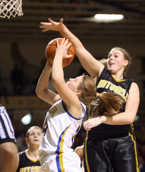 Aberdeen Central's Kelsey Hannigan, center, has her shot attempt blocked by Mitchell's Kristin Sabers, right, during a game last season at Golden Eagles Arena. The two teams square off against each other on Saturday at 7:30 p.m. at Golden Eagles Arena.