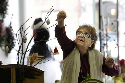 Linda Jordan of Vernon hangs an ornament on a display at Wicked Chic, a pop-up arts and craft shop on Main Street in Manchester.