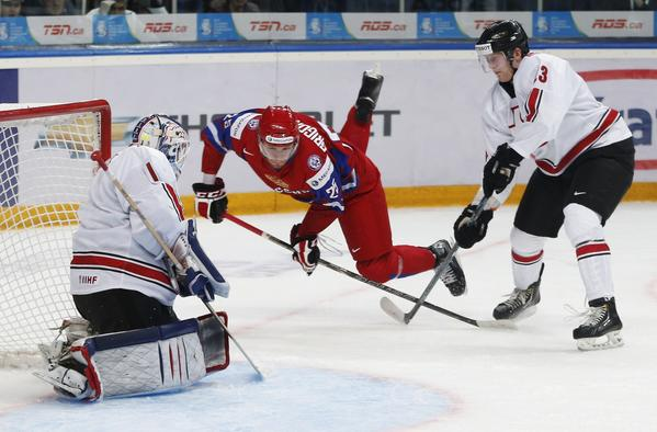 Russia's Mikhail Grigorenko goes flying through the air between Switzerland's goalie Melvin Nyffeler (L) and Martin Ness (R) during the second period of their quarter-final game at the 2013 IIHF U20 World Junior Hockey Championship in Ufa, January 2, 2013.