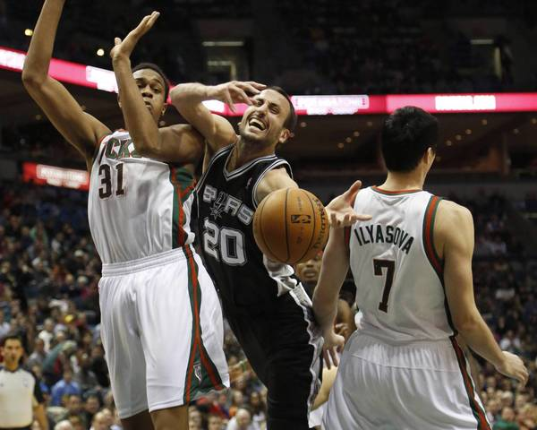 San Antonio Spurs guard Manu Ginobili (C) is fouled as he drives against Milwaukee Bucks forwards John Henson (L) and Ersan Ilyasova (R) during the second half of their NBA basketball game in Milwaukee, Wisconsin January 2, 2013.