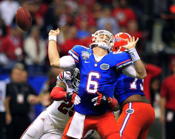 Florida Gators quarterback Jeff Driskel loses the ball as he is sacked in the third quarter by Louisville Cardinals safety Calvin Pryor (L) during the 2013 Allstate Sugar Bowl NCAA football game in New Orleans, Louisiana January 2, 2013.