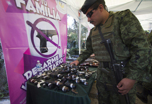 A member of the Mexican Army checks guns handed in as part of a an exchange program launched by government officials in the Iztapalapa borough of Mexico City.