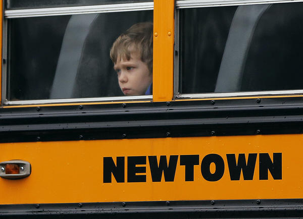 A child looks out of the window of a school bus carrying students from the Newtown school district as it makes its way past the funeral for Sandy Hook student James Mattioli. Sandy Hook Elementary School students returned to classes in a neighboring town Thursday.