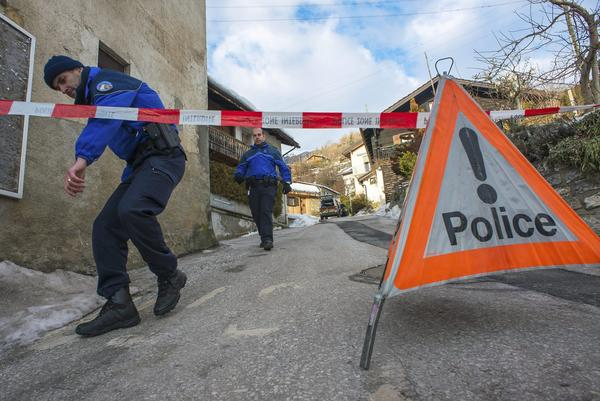 Police officers men walk in the village of Daillon, Switzerland, where three people were shot and killed.