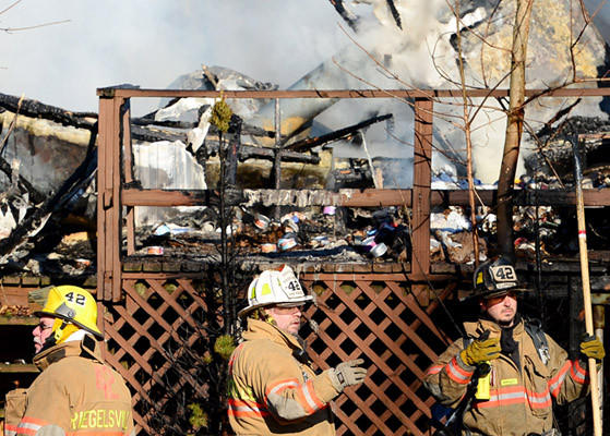 Firefighters battle a fire in a mobile home at 15 Royal Manor Road, Williams Township, Thursday.
