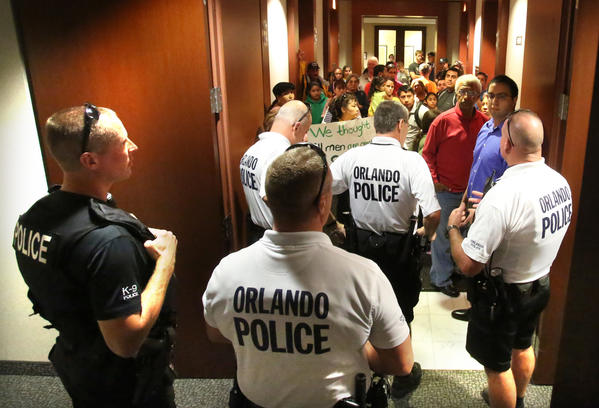 Orlando Police block the entrance in the hallway outside Sen. Marco Rubio's office as Hispanic immigration policy activists arrived unannounced at Rubio's office in downtown Orlando, Thursday, January 3, 2012. The group rallied in front of Orlando City Hall before marching to Rubio's office nearby.