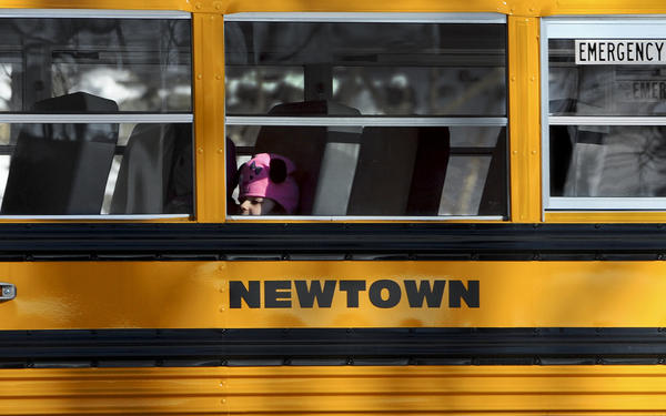A child sits on a Newtown bus leaving the new Sandy Hook Elementary School on the first day of classes in Monroe, Conn.