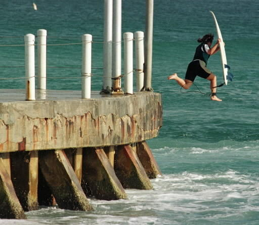 A surfer jumps off the Boynton Inlet pier.