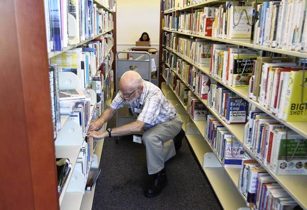 Ralph Rousseau shelves books in October at Cagan Crossings Community Library, which might see more budget cuts.